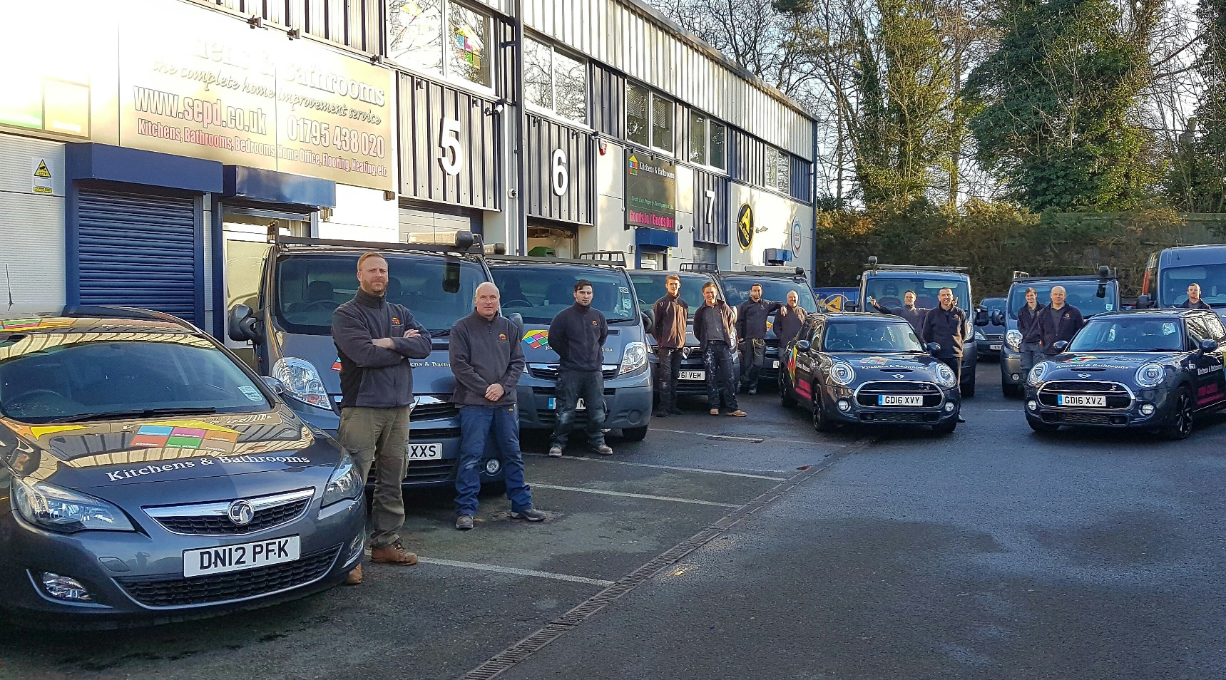 Kitchens & Bathrooms group photo with company vehicles.