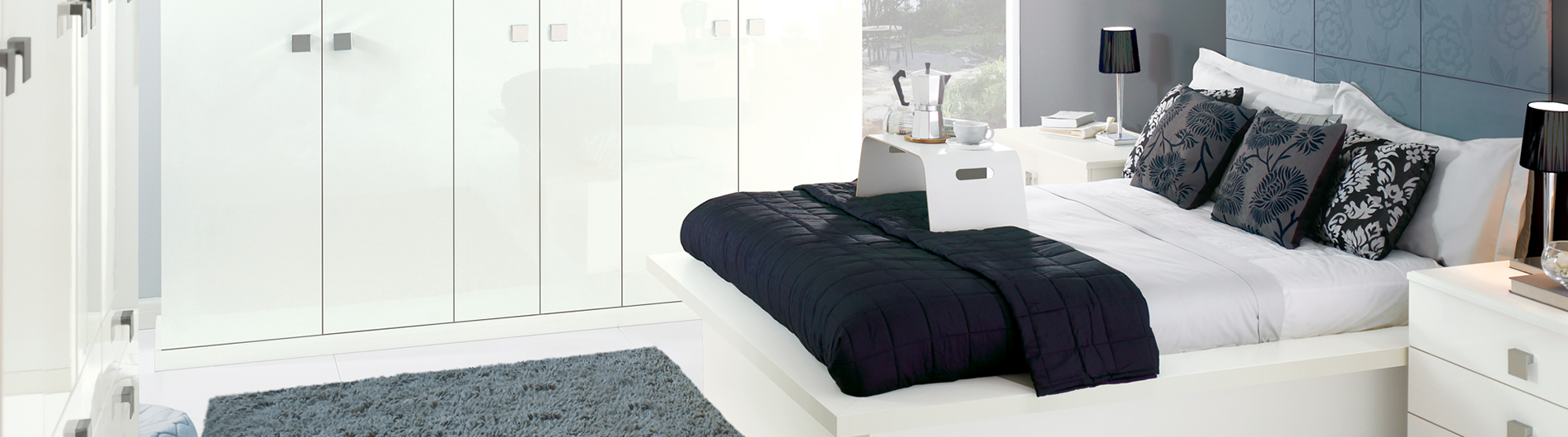 Blue, white and black colour themed bedroom with a breakfast tray stand on the bed.