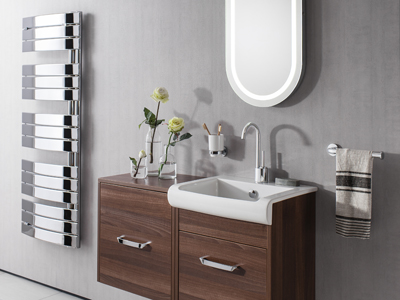 White sink with walnut cabinets below oval shaped mirror.